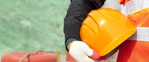Hand holding orange construction hat