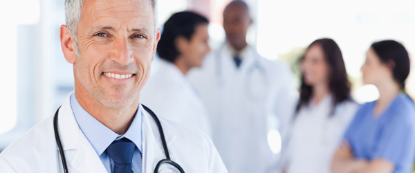 doctor smiling with other doctors in background