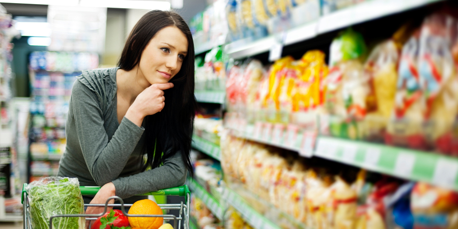 woman grocery shopping trying to make decision